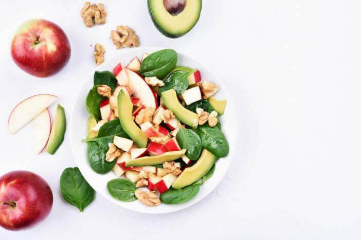 Huge bowl of salad with apples, avocado and nuts