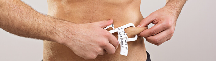 man measuring his body fat with a caliper