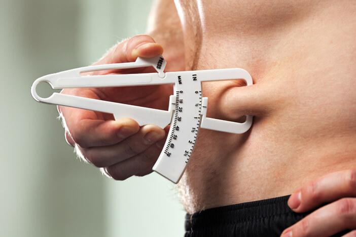 man measuring his body fat with a fat caliper